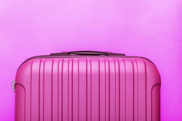 Moderne roze koffer op roze achtergrond close-up met kopie ruimte voor tekst. minimalistisch reisconcept.