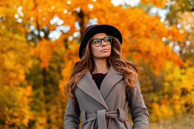 Moderne schattige jonge hipster vrouw met een stijlvol kapsel in een vintage hoed in een modieuze bril in een elegante jas loopt op een herfst park. trendy meisjesmodel geniet van een wandeling door het bos.