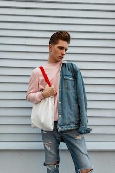 Moderne schattige jonge man in mode roze sweatshirt in stijlvol spijkerjack met vintage stoffen shopper staat in de buurt van witte muur in de stad. aantrekkelijke man in trendy jeans kleding buitenshuis. zomerse stijl.