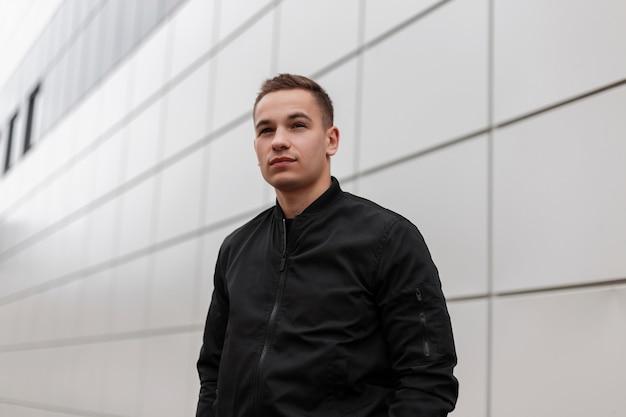 Moderne schattige jonge man met een stijlvol kapsel in een trendy lente-zwarte jas staat in de buurt van een grijs metalen gebouw in de stad.