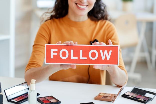 Moderne schoonheidsblogger zittend aan tafel met volg print teken, horizontaal schot