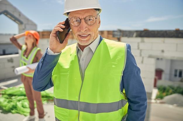 Moderne senior man in brillen met zijn mobiele telefoon vooruitkijkend