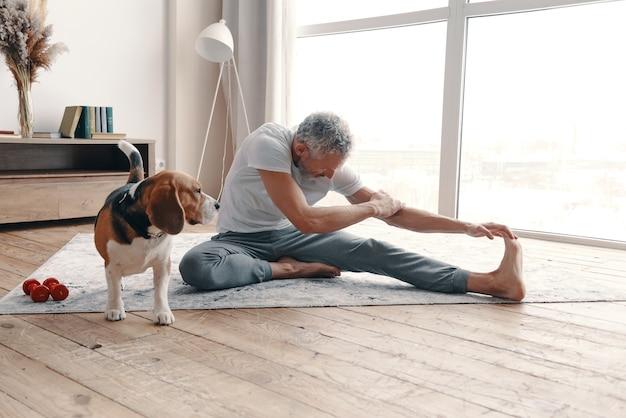Moderne senior man in sportkleding die thuis traint in de buurt van zijn hond
