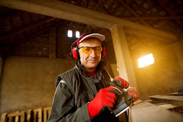 Moderne senior timmerman in een professionele uniform en bescherming werken met een elektrisch gereedschap op een houten pallet.