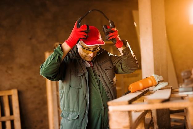 Moderne senior timmerman in een professionele uniform opstijgen gehoorbescherming terwijl je in de buurt van elektrisch gereedschap op een houten pallet.