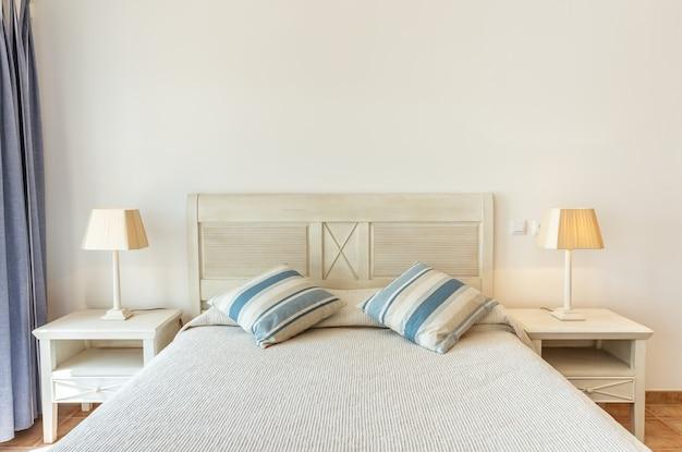 Moderne slaapkamer met lampenkappen, frontaal gefotografeerd.