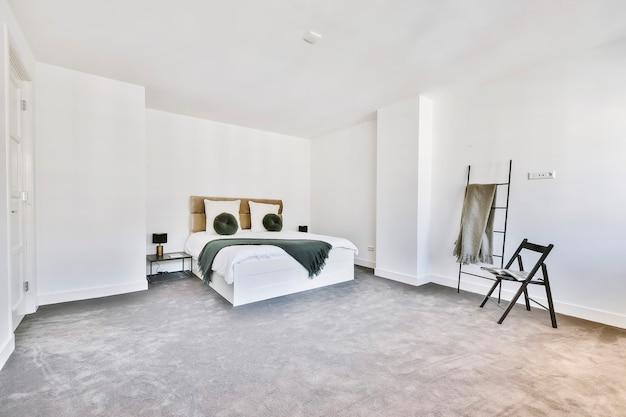 Moderne slaapkamer met witte muren en zachte grijze vloerbedekking ingericht met knus bed en stoel met rek opzij