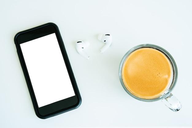 Moderne smartphone en echte draadloze in-ear hoofdtelefoon achtergelaten op tafel met een kopje espressokoffie van dichtbij. 's ochtends online een podcast luisteren tijdens het drinken van een kopje koffie.
