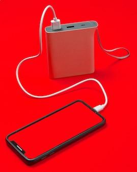 Moderne smartphone opladen met powerbank geïsoleerd