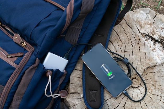 Moderne smartphone wordt opgeladen vanaf een powerbank die naast de rugzak op een houten stronk ligt