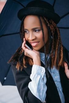 Moderne sociale communicatie. gelukkig zwarte vrouw. humeurig weer, vrolijke afro-amerikaanse vrouw met een paraplu op regenachtige dag, geluksconcept