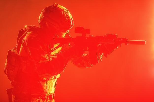 Moderne soldaat van de speciale strijdkrachten van het leger, politie-antiterroristische squadronjager in gevechtsuniform, helm met nachtzichtapparaat gericht op een aanvalsgeweer met korte loop, rustige studio-opname met rode achtergrondverlichting