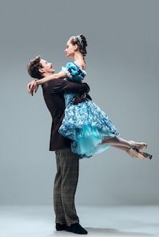 Moderne sprookjes. mooie eigentijdse ballroomdansers die op grijze studioachtergrond worden geïsoleerd. sensuele professionele artiesten die wals, tango, slowfox en quickstep dansen. flexibel en gewichtloos.