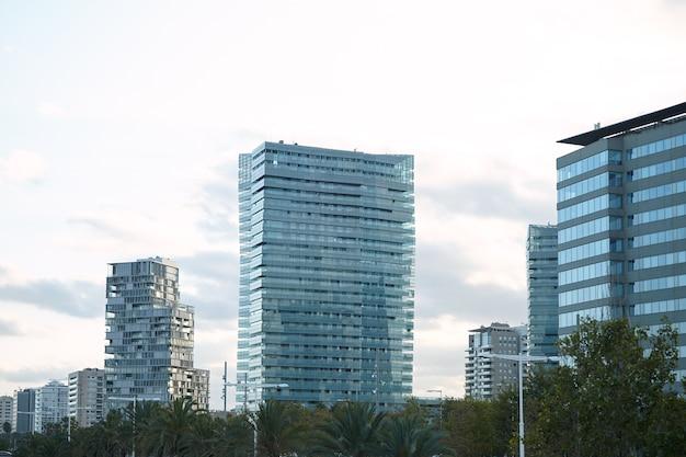 Moderne stadsgebouwen van glas en beton minuten na zonsondergang tegen een heldere witte hemel