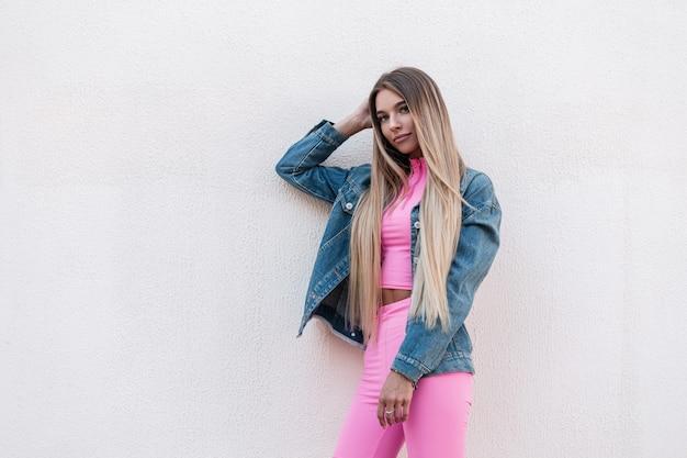 Moderne stedelijke jonge vrouw met chique lang haar in een blauwe modieuze denim jasje in een glamoureuze roze sportpak vormt in de buurt van een gebouw in de stad. europees stijlvol blond meisje buitenshuis. retro stijl.
