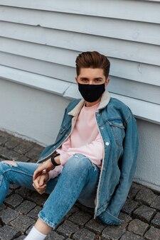 Moderne stijlvolle jongeman in denim modieuze blauwe vrijetijdskleding in beschermend zwart masker rust in de buurt van het gebouw op straat in de stad. trendy mannequin is beschermd tegen coronavirus. mode 2020.