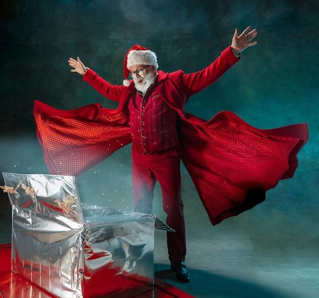 Moderne stijlvolle kerstman geïsoleerd op een donkere achtergrond, copyspace