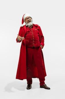 Moderne stijlvolle kerstman in rood modieus pak geïsoleerd op een witte achtergrond