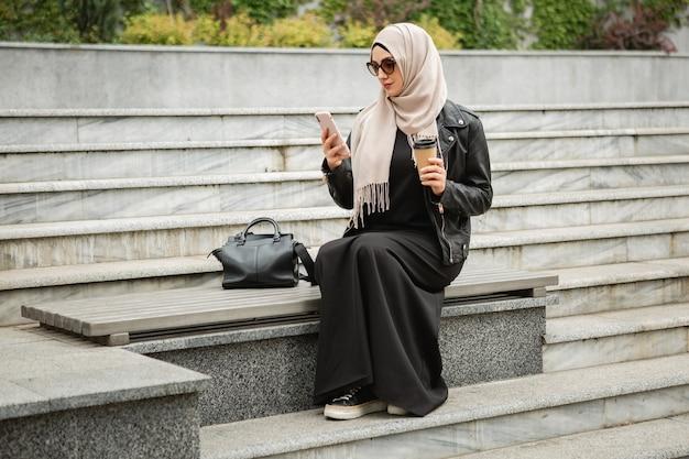 Moderne stijlvolle moslimvrouw in hijab, leren jas en zwarte abaya zittend in stadsstraat met mobiele telefoon in zonnebril