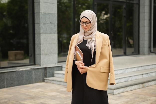Moderne stijlvolle moslimvrouw in hijab, zakelijke stijl jas en zwarte abaya wandelen in de stad straat met laptop