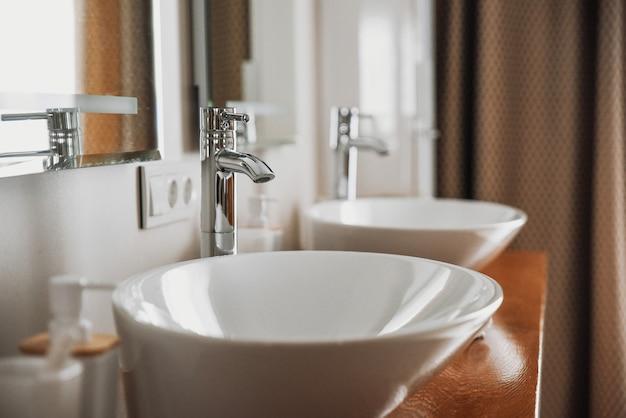 Moderne stijlvolle wastafels met chromen kranen.