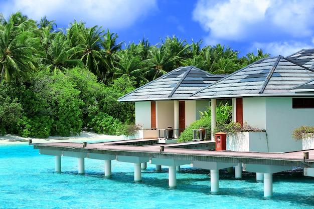 Moderne strandhuizen op palen in tropische resort