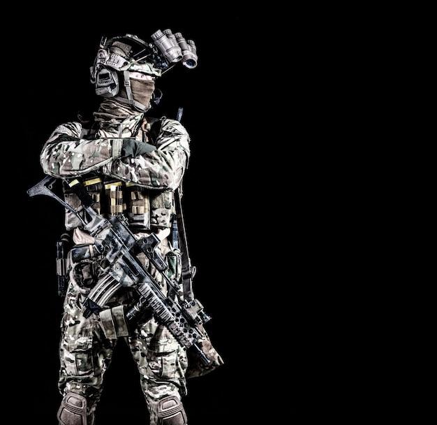 Moderne strijder, soldaat van de speciale troepenmacht, contraterroristische ploeg mender in volledige munitie, gezicht achter masker verbergen, uitgerust nachtzichtapparaat, staande met gekruiste armen op borst, copyspace