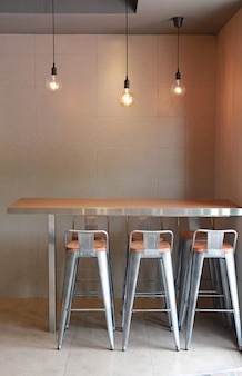 Moderne tafel tegen bar met stoelen loft interieur met grijze tegelmuur en opknoping decor lampen.
