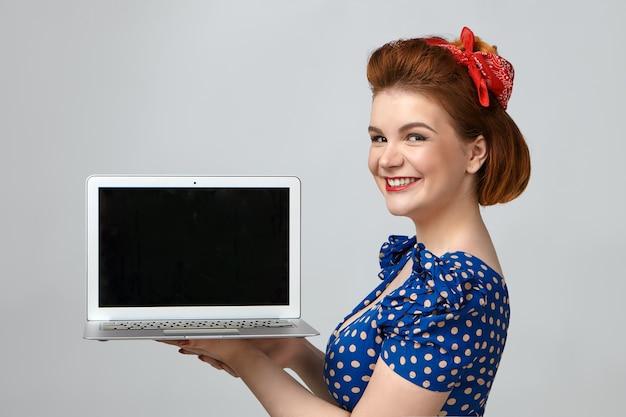 Moderne technologie en communicatie. geïsoleerd schot van aantrekkelijk glamoureus jong europees vrouwelijk model dat reclame maakt voor nieuw elektronisch apparaat