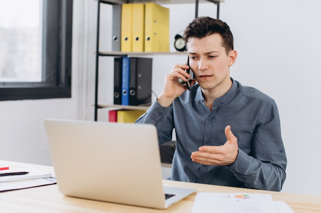 Moderne technologie en communicatieconcept. knappe ongeschoren jonge zakenmanwerknemer die aan generische laptop computer werkt en telefoongesprek in bureau heeft