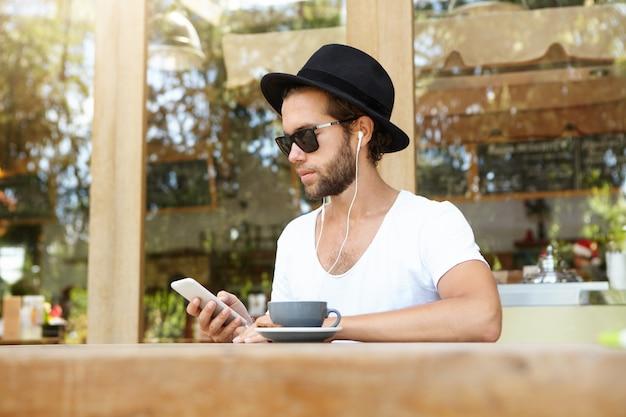 Moderne technologie en communicatieconcept. knappe student die in witte oortelefoons bij openluchtkoffiewinkel ontspannen die videogesprek voeren