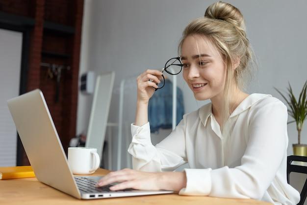 Moderne technologie, gadgets, baan en communicatieconcept. gelukkig charmante jonge vrouw met haar broodje ronde brillen houden en toetsen op laptop pc, surfen op internet, online chatten