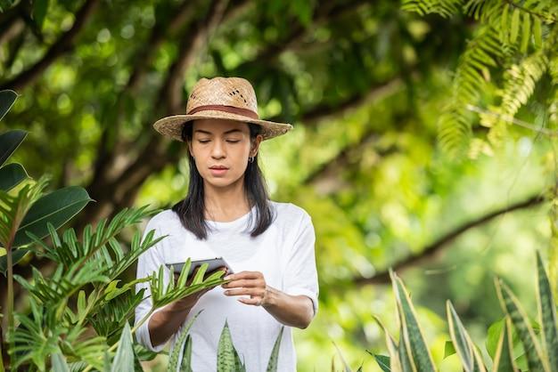 Moderne technologie in tuinieren. jonge vrouw met digitale tablet werken in een tuincentrum. milieuactivist met behulp van digitale tablet. vrouw tuinieren buiten in de zomer natuur.