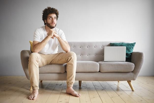 Moderne technologie, mensen en levensstijlconcept. portret van aantrekkelijke jonge ongeschoren man met volumineus haar en blote voeten met vermoeide uitdrukking, opzoeken tijdens het werken op laptop op bank