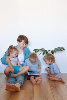 Moderne technologieën in het dagelijks leven een vrouw en kinderen kijken naar een tablet op de vloer. hobby's en recreatie met gadgets. familievakantie, breng tijd moeder en zoon samen thuis door.