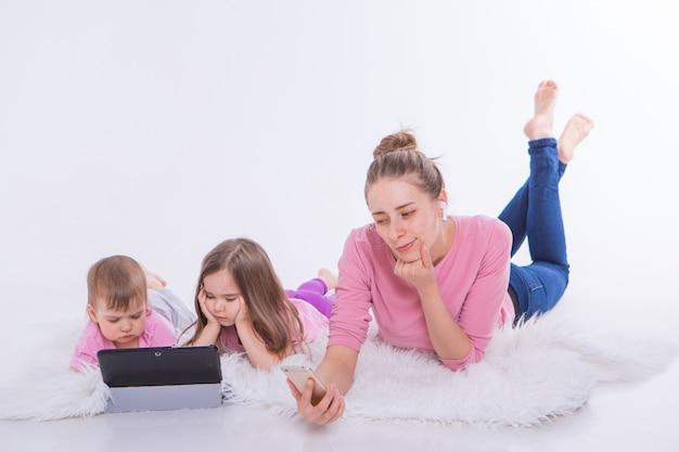 Moderne technologieën in het dagelijks leven: vrouw praat via telefoon via headset, kinderen kijken cartoon op tablet. hobby's en recreatie met gadgets. familie vakantie. ouders met meisjes op verdieping