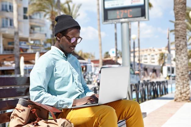 Moderne technologieën, mensen en stedelijke levensstijl. aantrekkelijke jonge afro-amerikaanse blogger die werkt aan nieuw artikel met behulp van generieke notebook pc tijdens vakanties in de badplaats, met een geïnspireerde look