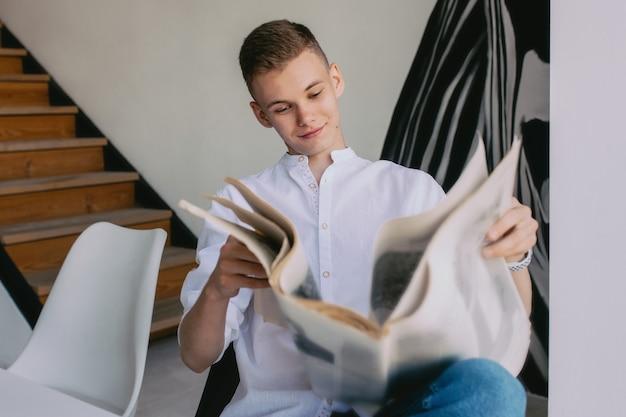 Moderne tiener man leest papieren krant tijdens het ontbijt thuis