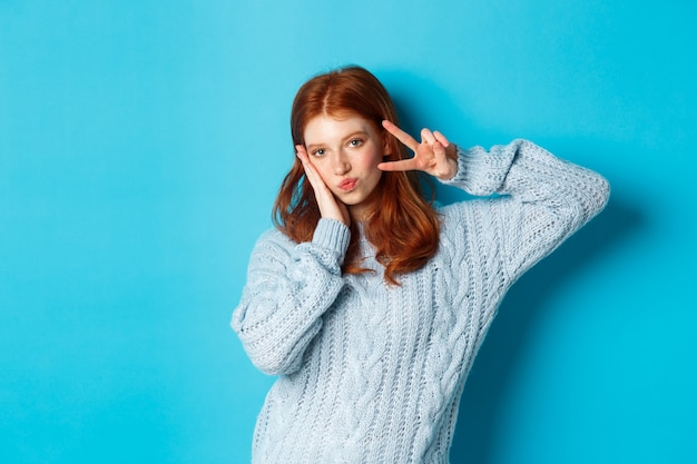 Moderne tiener meisje met rood haar, vredesteken tonen en poseren in trui tegen blauwe achtergrond.