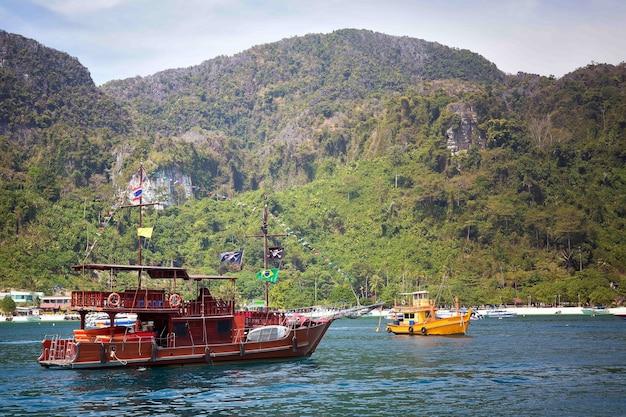 Moderne toeristenboot gestileerd als een piratenschip tegen de achtergrond van een rotsachtige kust