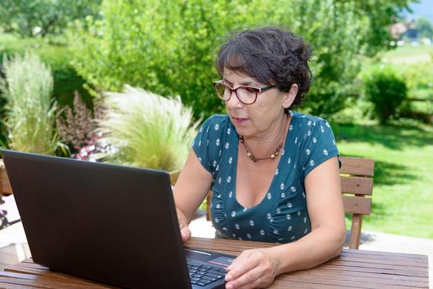 Moderne toevallige vrouwenzitting bij tuin met laptop