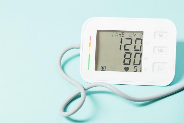 Moderne tonometer op blauwe achtergrond, druk 120 tot 80 op monitor
