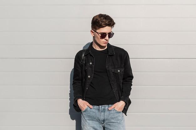 Moderne trendy jonge man in modieuze denim kleding in stijlvolle zonnebril