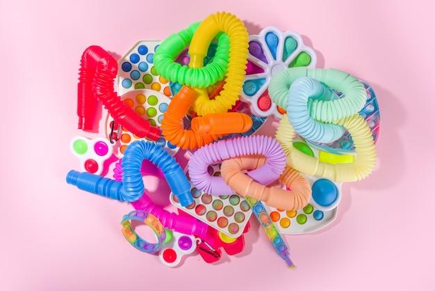 Moderne trendy kids fidget vinger speelgoed, ontspanning concept - set van verschillende heldere pop-it, simple-dimple, squishy, pop-tubes, op kleurrijke roze achtergrond, bovenaanzicht kopie ruimte