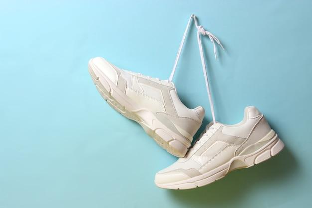 Moderne trendy sneakers hangen aan veters op een gekleurde achtergrond vrijetijdsschoenen sportschoenen