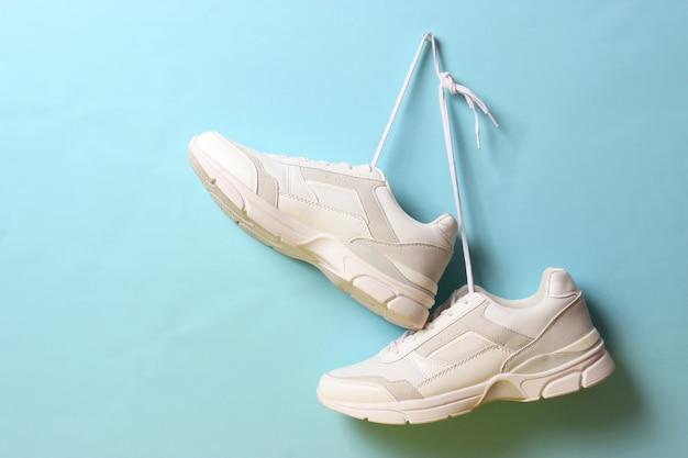 Moderne trendy sneakers hangen aan veters op een gekleurde achtergrond Premium Foto