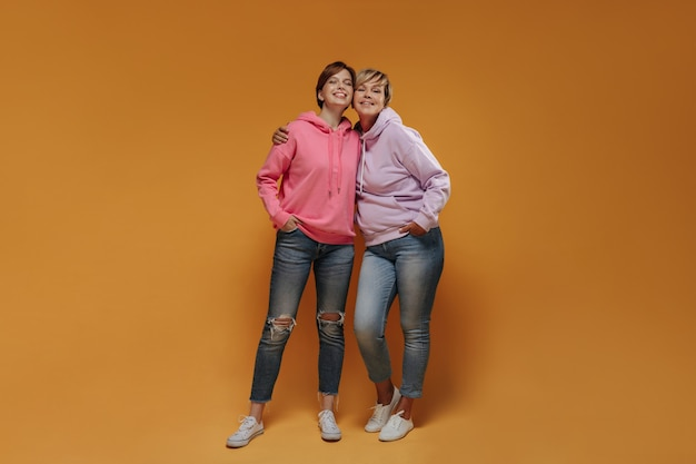 Moderne twee vrouwen met coole korte haarstijl in brede roze hoodies, skinny jeans en witte sneakers op zoek naar camera en lachend.