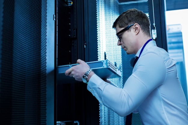 Moderne uitrusting. ernstige professionele operator die werkt met serverapparatuur op kantoor