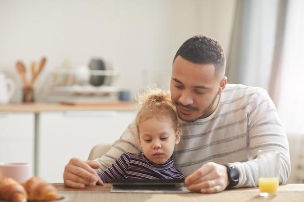 Moderne vader met behulp van digitale tablet met schattig klein meisje