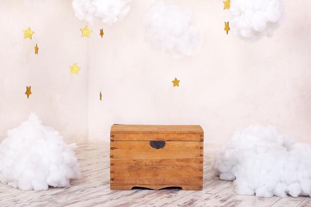 Moderne vintage interieur van kinderkamer met een oude houten kist van een getextureerde muur met wolken. speeltuin interieur. kist voor speelgoed en spelletjes voor kinderen. kinderkamer inrichting
